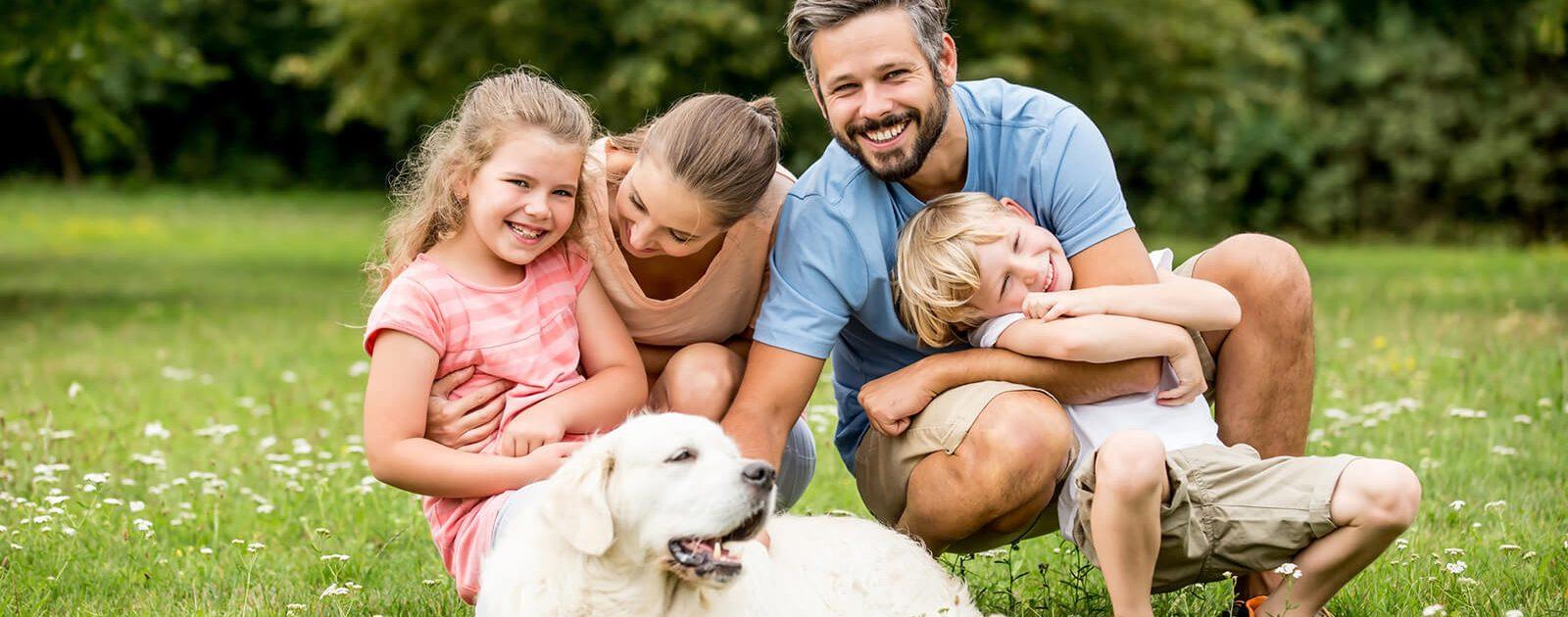 Wie entsteht Heuschnupfen? Familie mit Hund liegt auf der Wiese