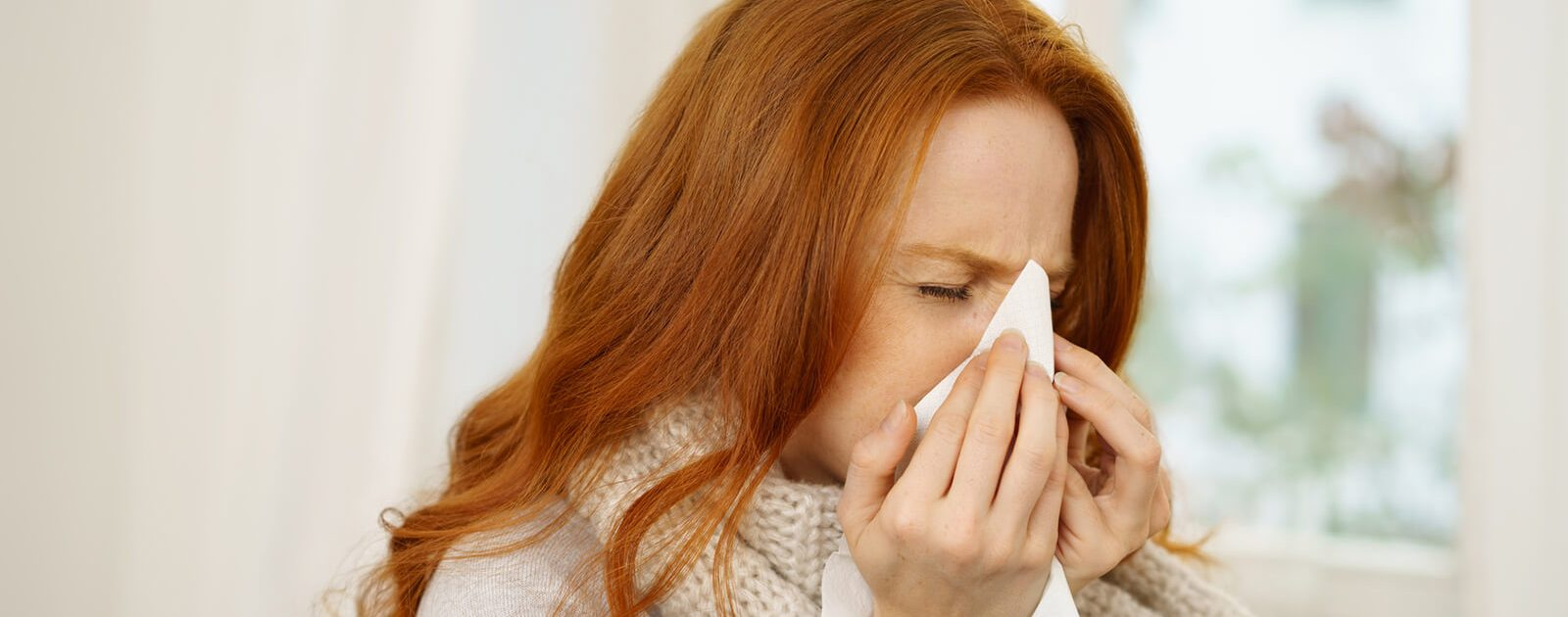 Eine Frau mit Schnupfen als Nasenbeschwerde.
