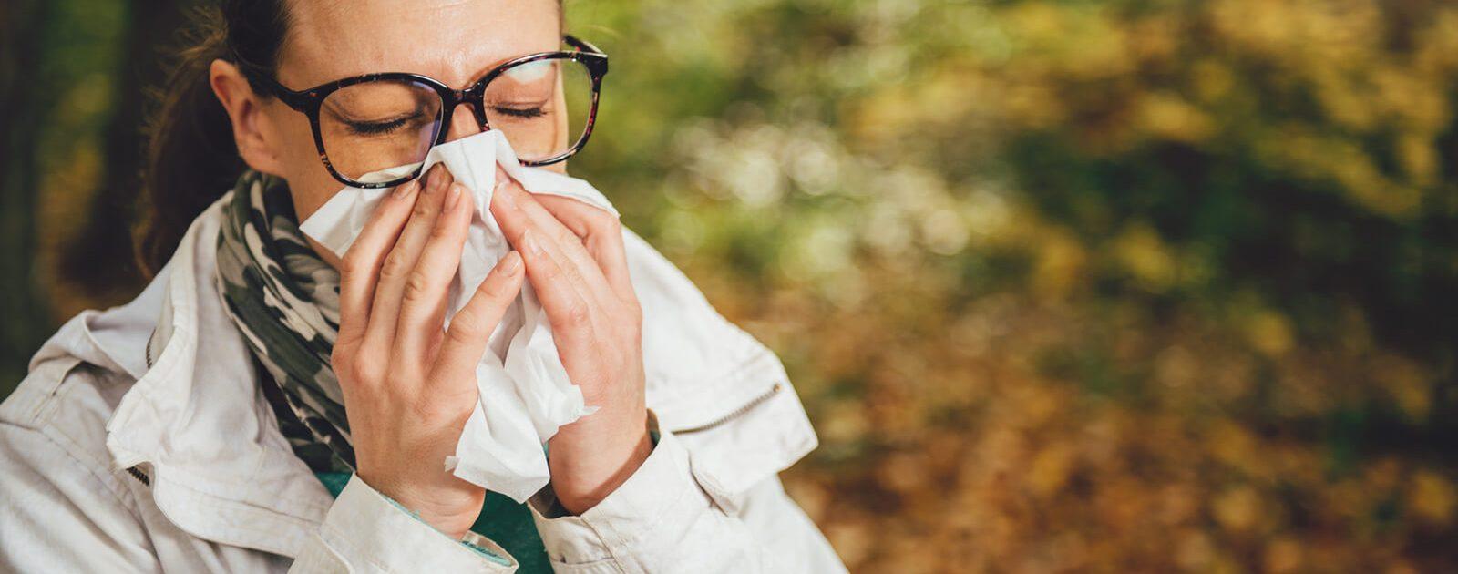 Eine Frau mit chronischem Schnupfen schnäuzt in ein Taschentuch.