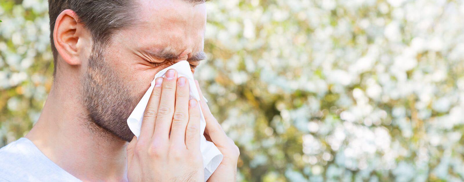 Ein Mann niest, weil er Heuschnupfen hat.