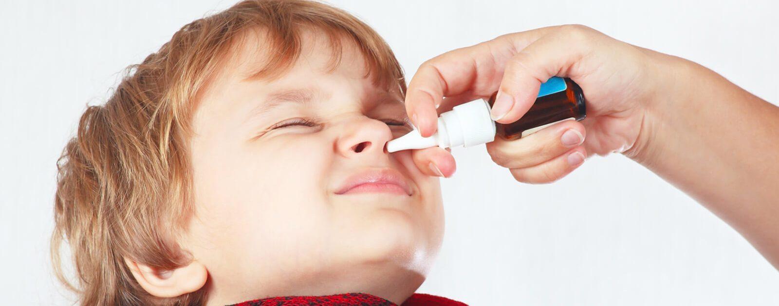 Junge verwendet Nasenspray ohne Konservierungsstoffe.