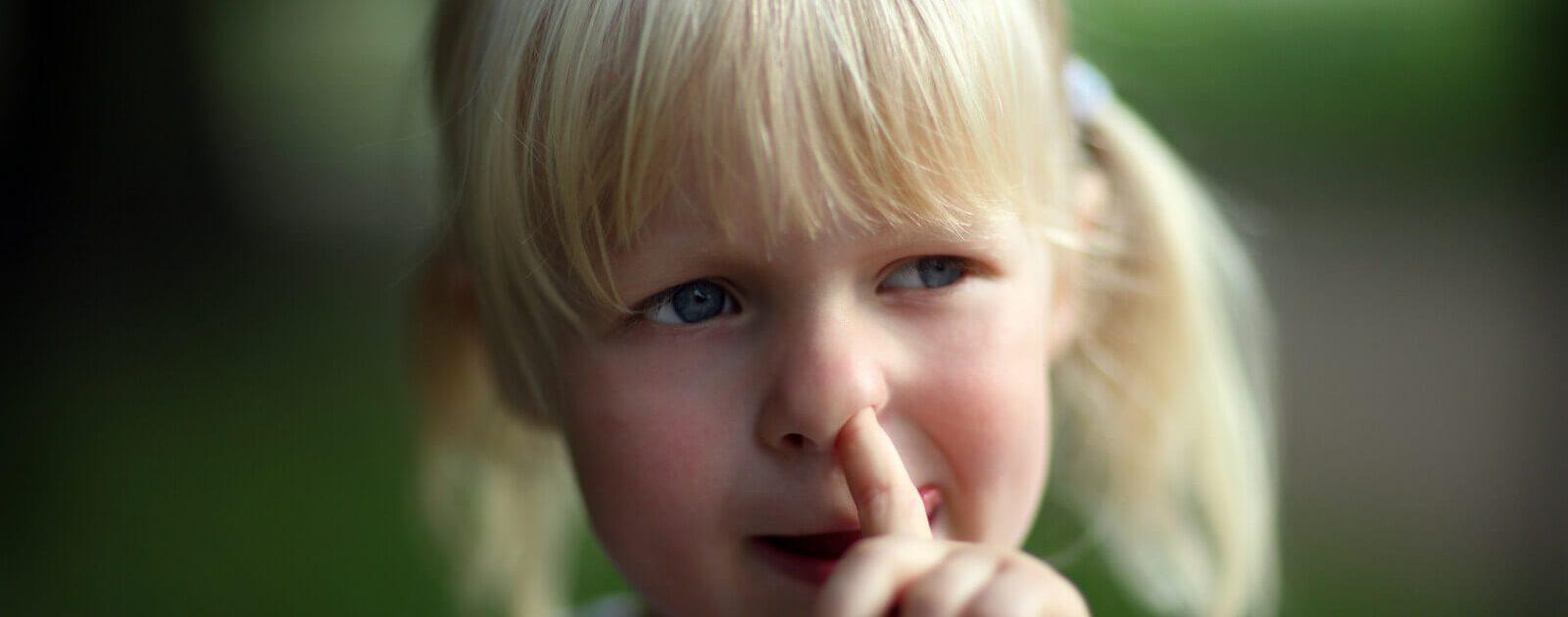 Ein kleines Mädchen beim Nasenbohren.