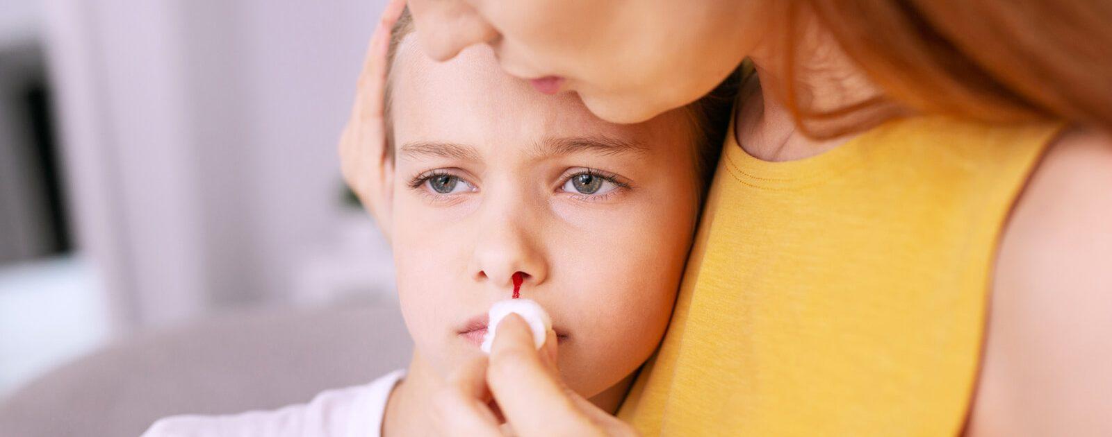 Frau stoppt das Nasenbluten ihres Kindes.