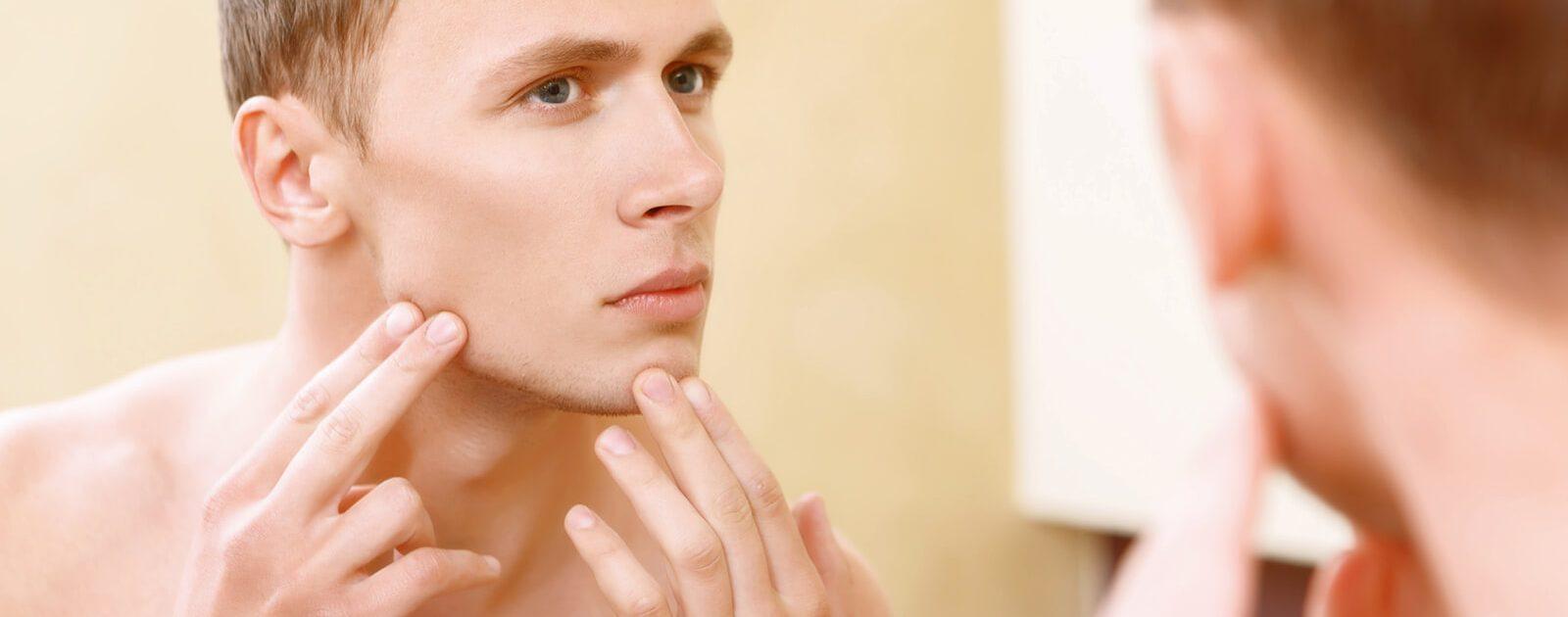 Mann sieht in den Spiegel und sucht nach Nasenfurunkel.