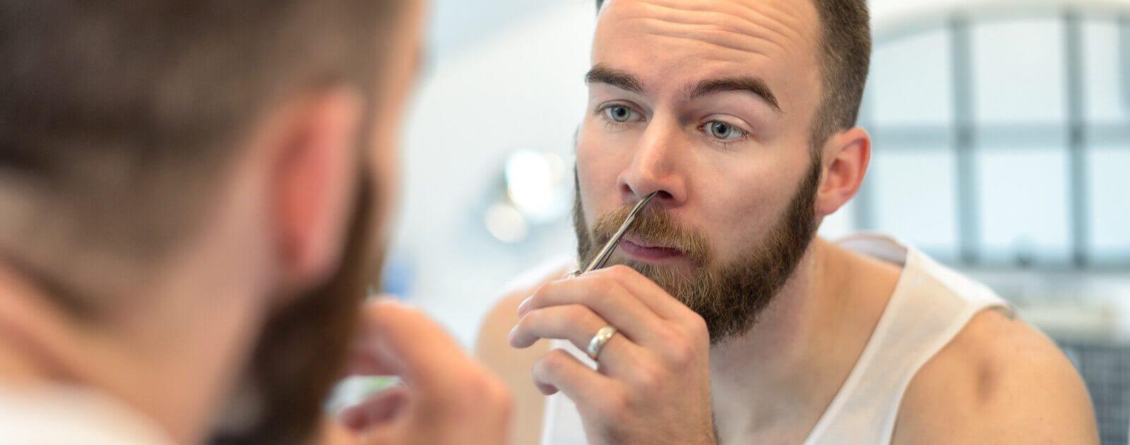 Mann kürzt sich seine Nasenhaare mit einer Schere