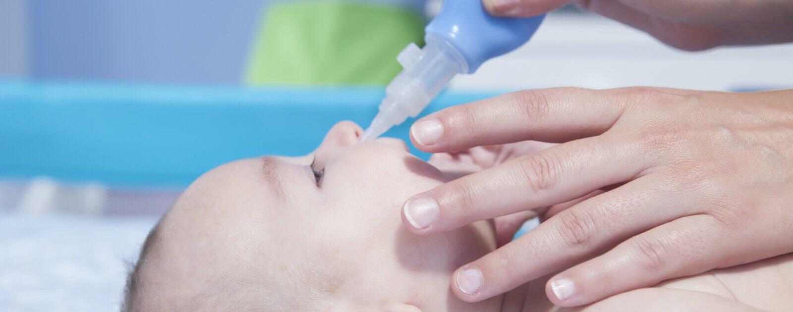 Mit einem Nasensauger befreit eine Mutter ihr Kind von Verstopfungen in der Nase.