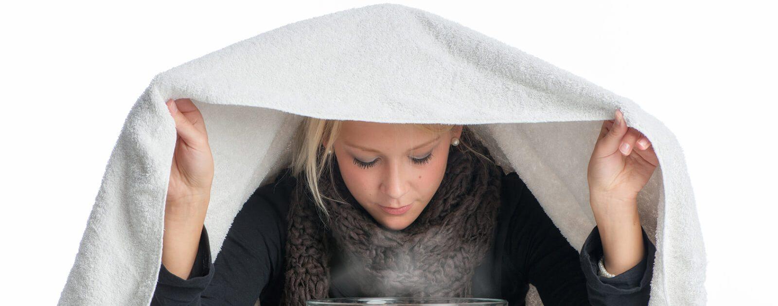 Frau inhaliert, aufgrund einer Entzündung der Nasenschleimhaut