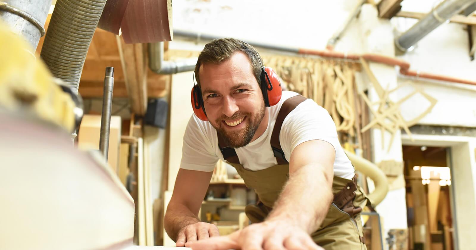 Mann sägt Holz bei der Arbeit: Das Risiko auf Tumoren in der Nase beim ständigen Einatmen von Holzstaub steigt.