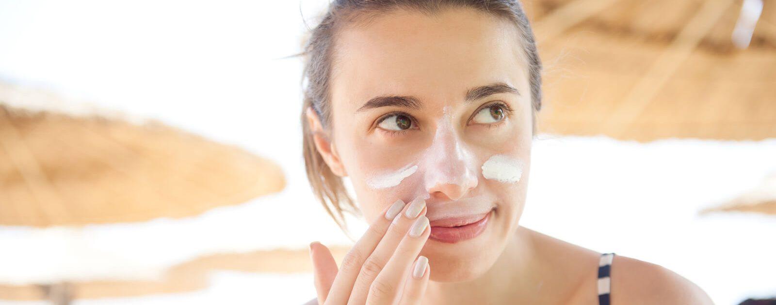 Frau beugt mit Sonnencreme einem Basaliom an der Nase vor.