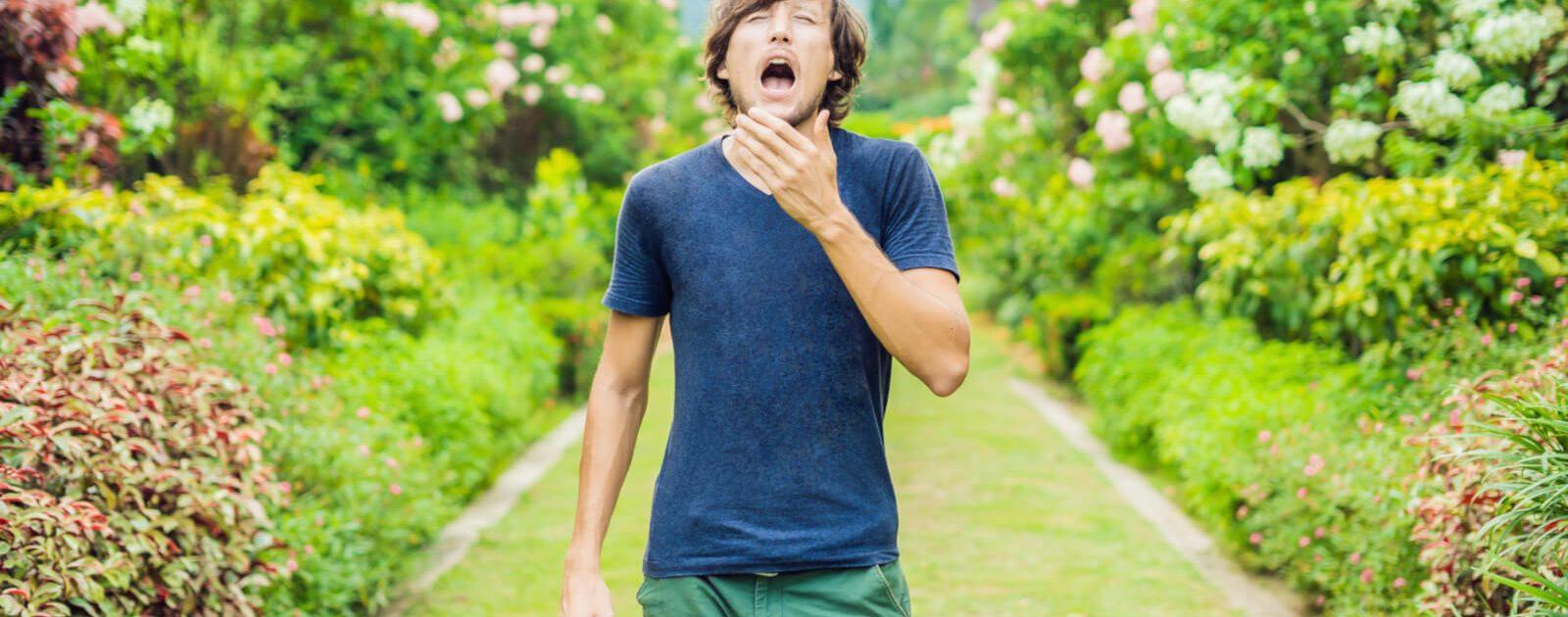 Mann muss wegen dem photischen Niesreflex niesen.