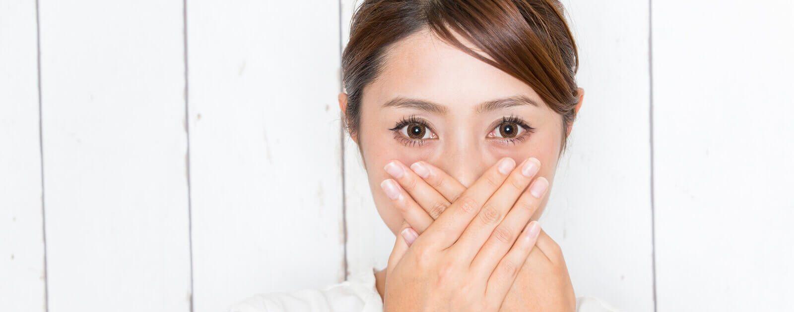 Frau mit Pickel in der Nase hält sich die Hand vor die Nase