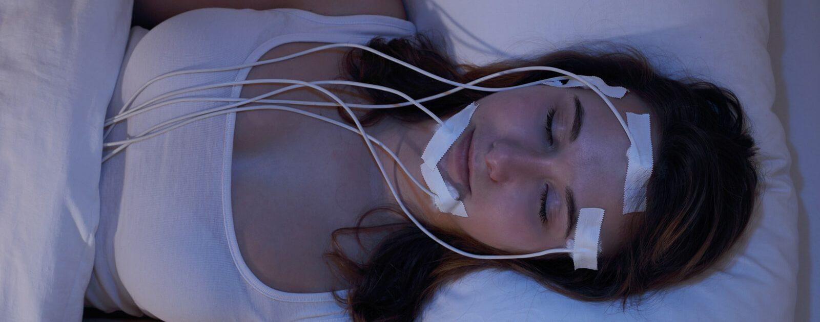 Frau im Schlaflabor mit Messinstrumenten
