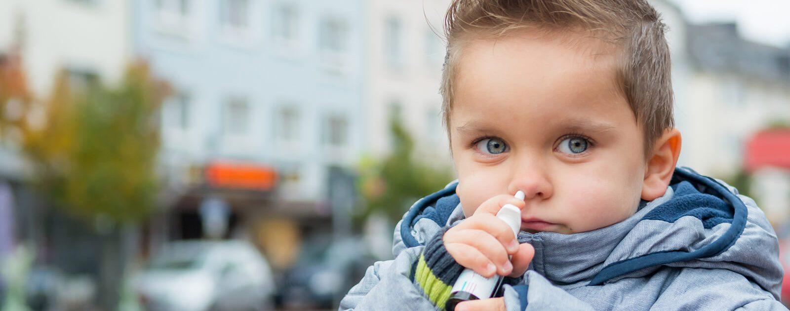 Ein kleiner Junge behandelt seinen Schnupfen mit einem Nasenspray