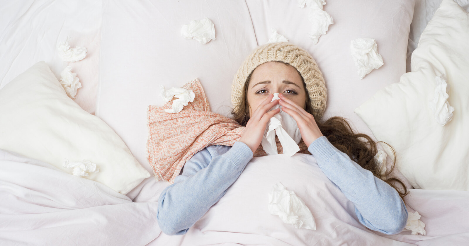 Frau mit Schnupfen putzt sich mit einem Taschentuch das Nasensekret aus der verstopften Nase.
