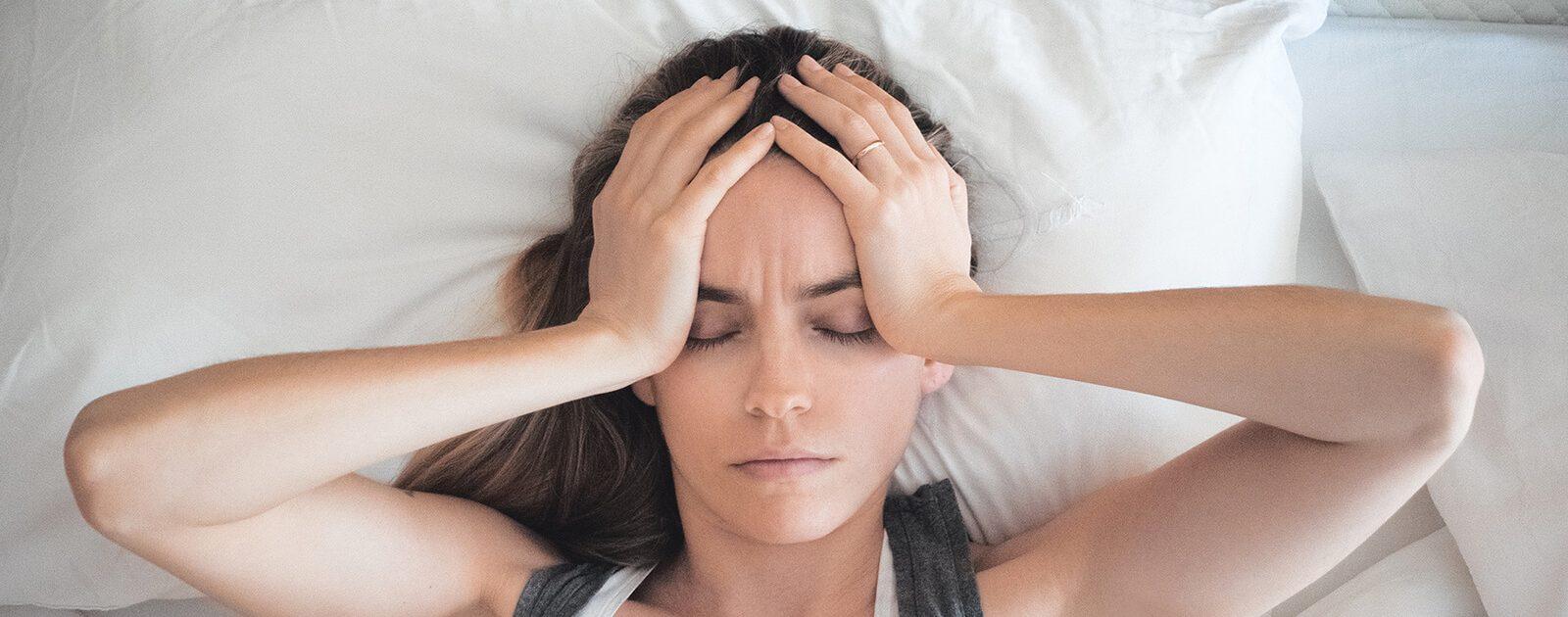 Frau liegt im Bett: Sie leidet an einer Stirnhöhlenentzündung.