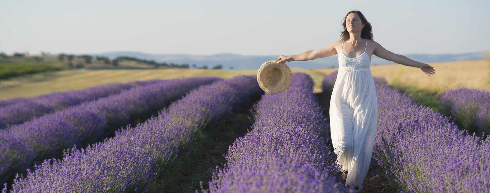Geruchssinn und Geschmackssinn testen. Frau spaziert durch ein Lavendelfeld.