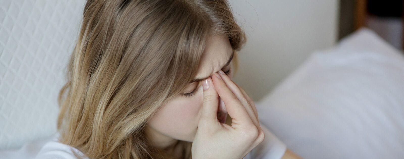 Frau fasst sich an die Nase wegen trockener Nasenschleimhaut.