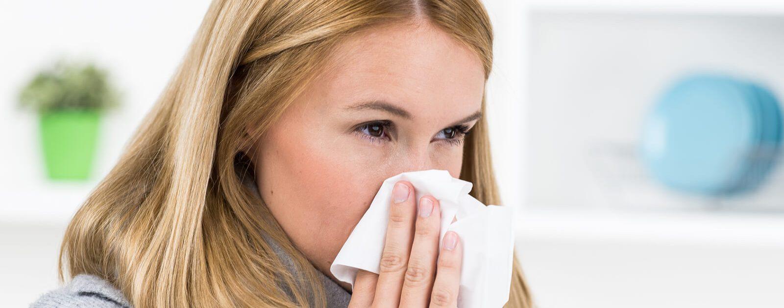 Eine Frau mit vasomotorischer Rhinitis schnäutzt in ein Taschentuch.