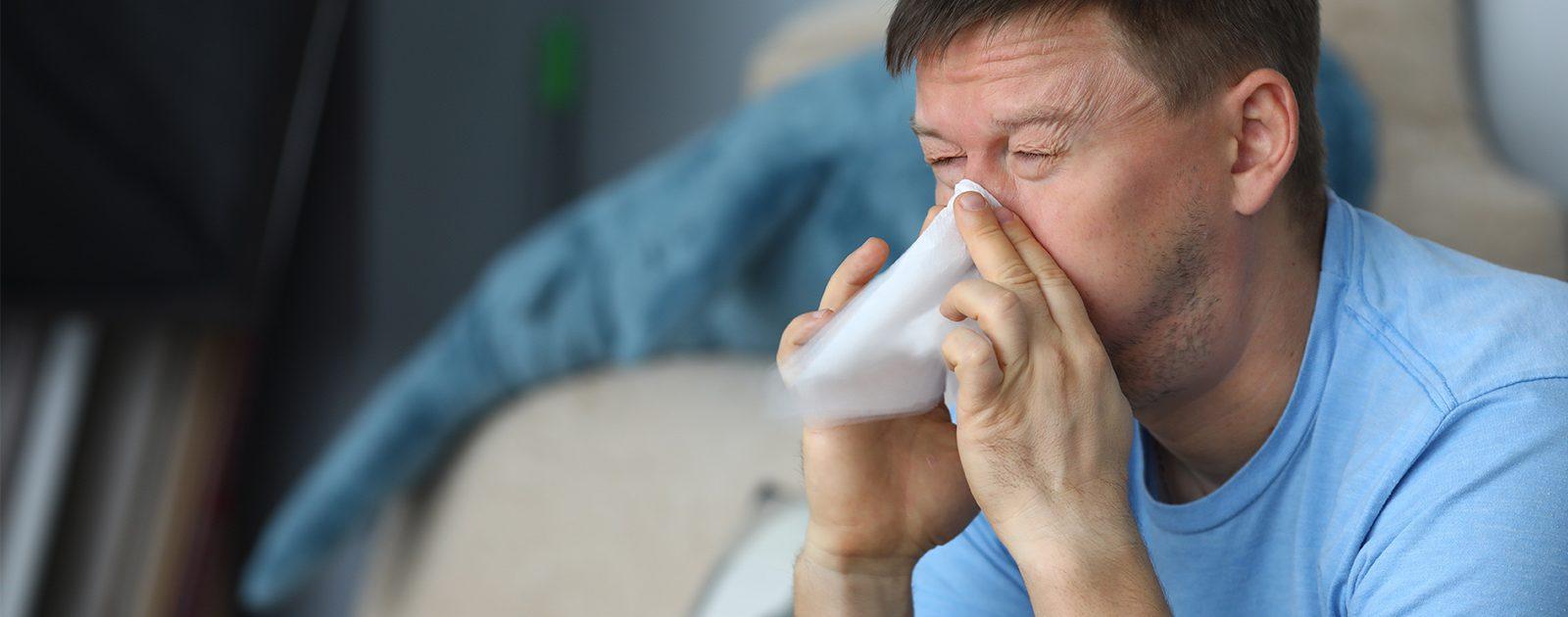 Mann leidet aufgrund seiner Hausstauballergie unter einer laufenden Nase und schnäuzt sich.