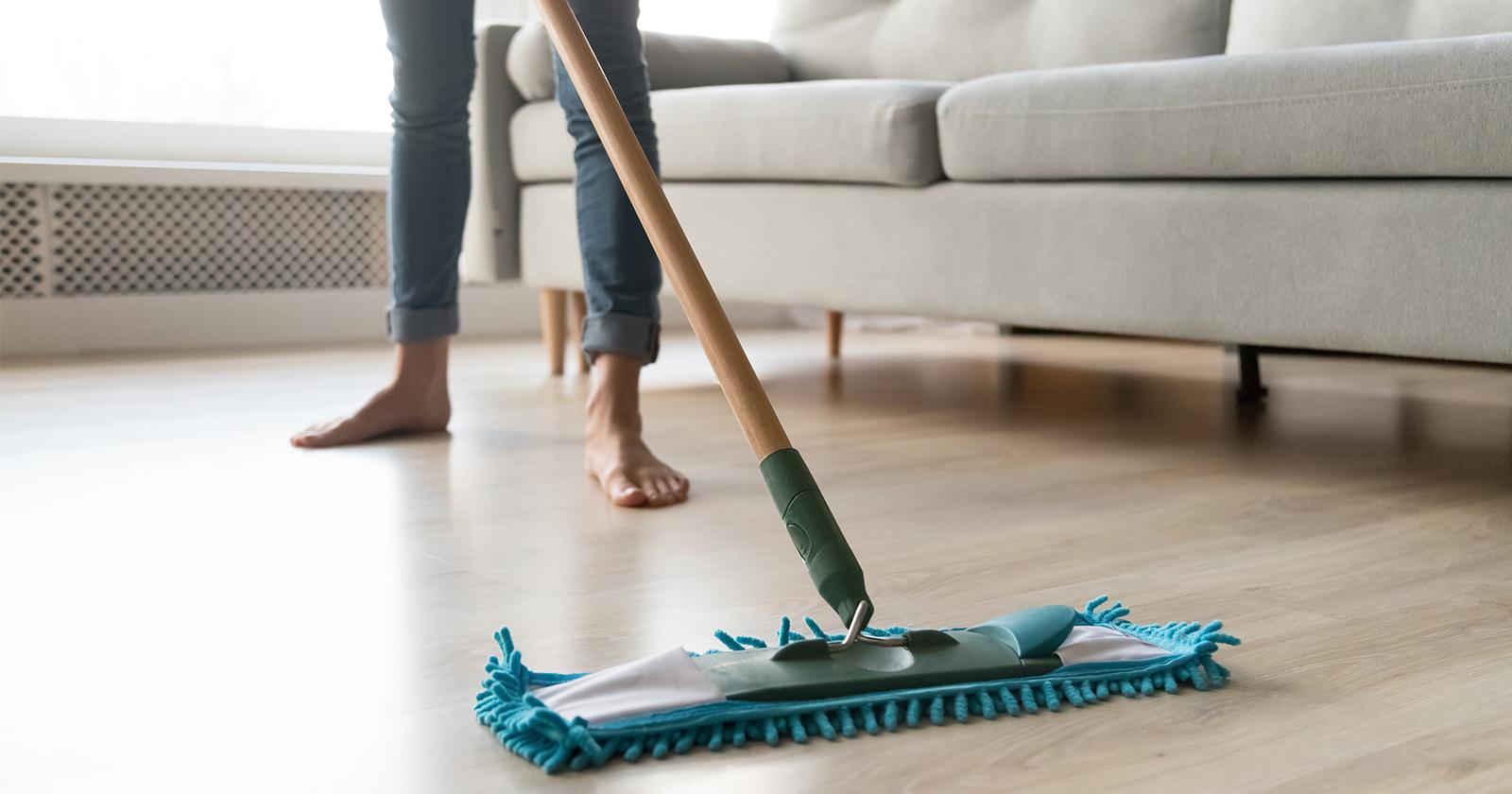 Frau wischt den Fußboden, um Staub zu entfernen, der eine Hausstauballergie begünstigen könnte.