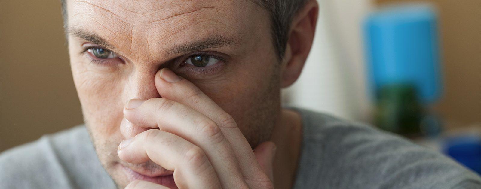 Mann, der an Rhinitis sicca leidet, fasst sich an die Nase.